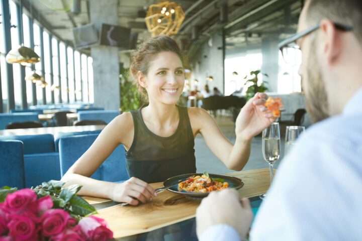 Cheerful young woman giving her food to boyfriend to taste during romantic dinner in restaurant