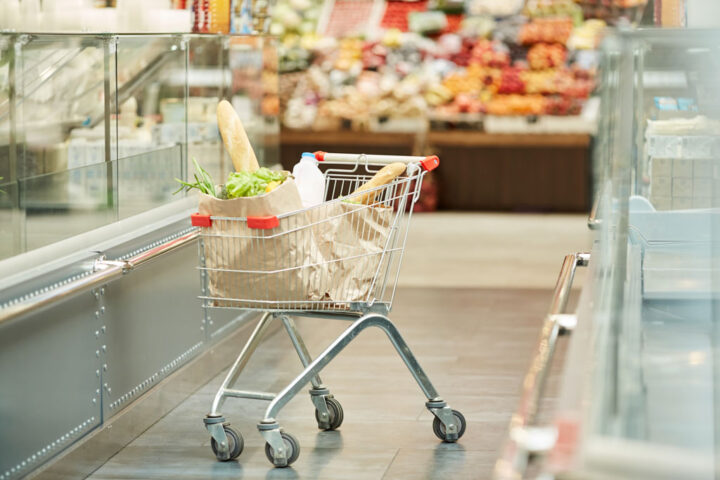 shopping cart with groceries standing in supermarket