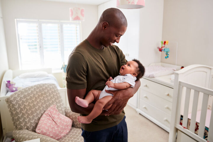 Proud Father Cuddling Baby Son In Nursery At Home