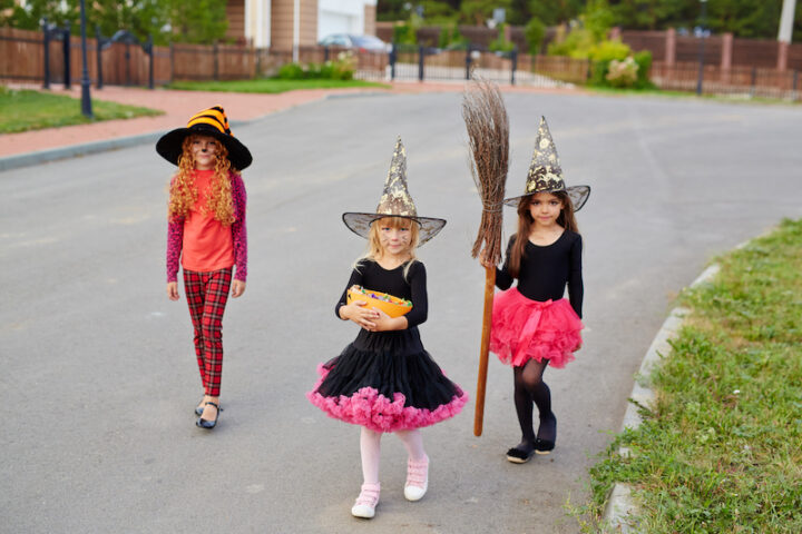 Halloween kids walking down road and asking for a treat