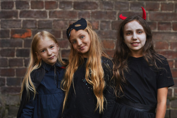 Waist up portrait of three girls dressed in Halloween costumes looking at camera while posing against brick wall outdoors
