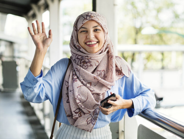 Smiling Muslim woman waving