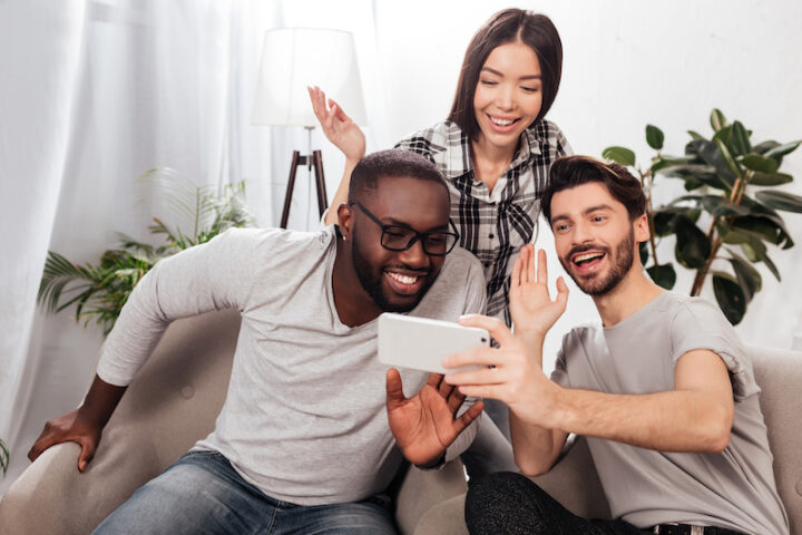 Portrait of three smiling friends sitting on chairs at home and joyfully waving hello gesture while looking in mobile phone together isolated