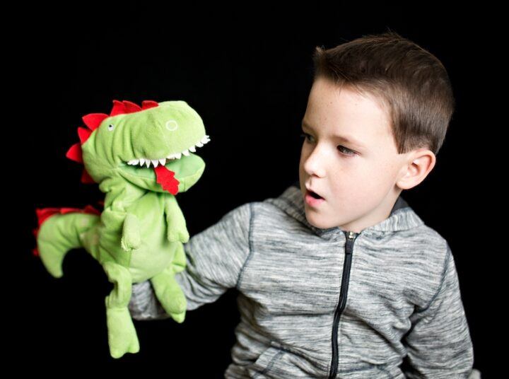 kid playing with a plush poppet resembling a dragon.