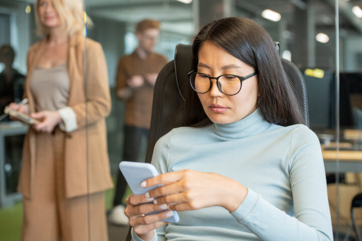 Young Asian businesswoman in blue turtleneck pullover using smartphone while looking through online reviews or videos at break in office