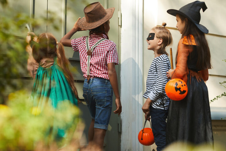 Group of children in Halloween costumes knocking in the door and say trick or treat