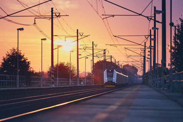 train arriving at platform with sunset in the background