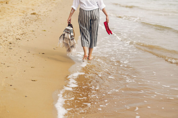 Woman walking barefoot on beach, with shoes and bag in hands