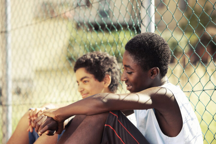 Two young African boys resting outdoors on a sunny day