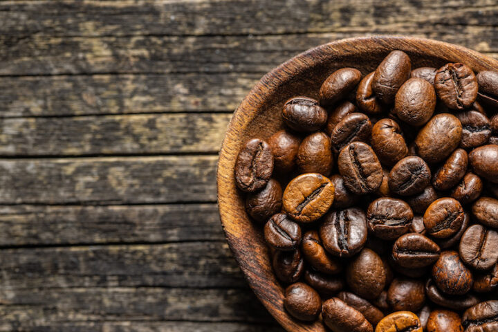 Roasted coffee beans on old wooden table. Top view.
