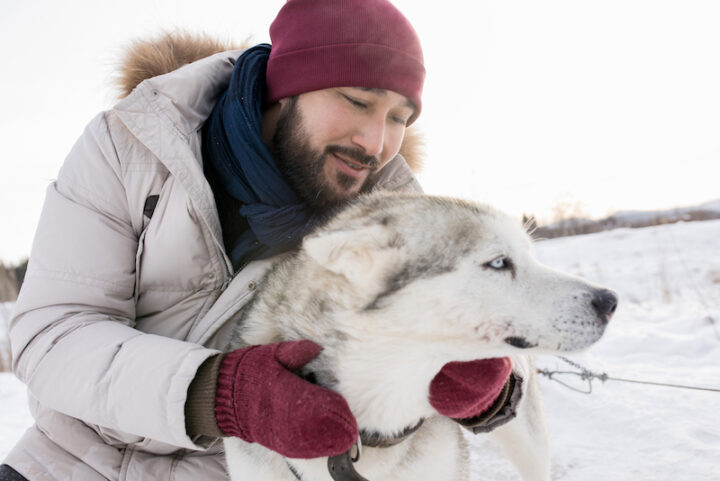 male owner and his Siberian husky dog in the snow