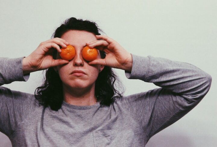 Woman with oranges covering her eyes