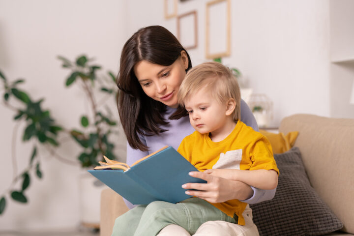 Content beautiful young mother sitting on sofa in living room and reading fairy tale to blond-haired son