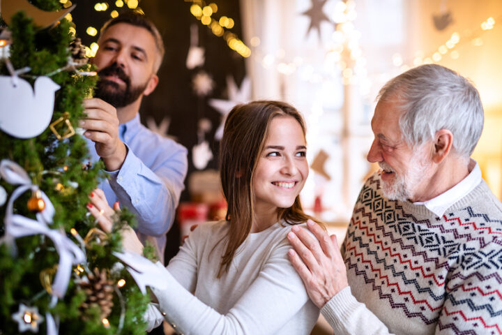 Happy men and woman family relatives indoors at home at Christmas, decorating tree.