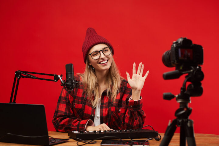 Young woman sitting at the table she working as a radio dj she smiling and waving to the camera at studio