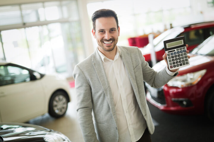 Car salesman calculating a price at the modern dealership office
