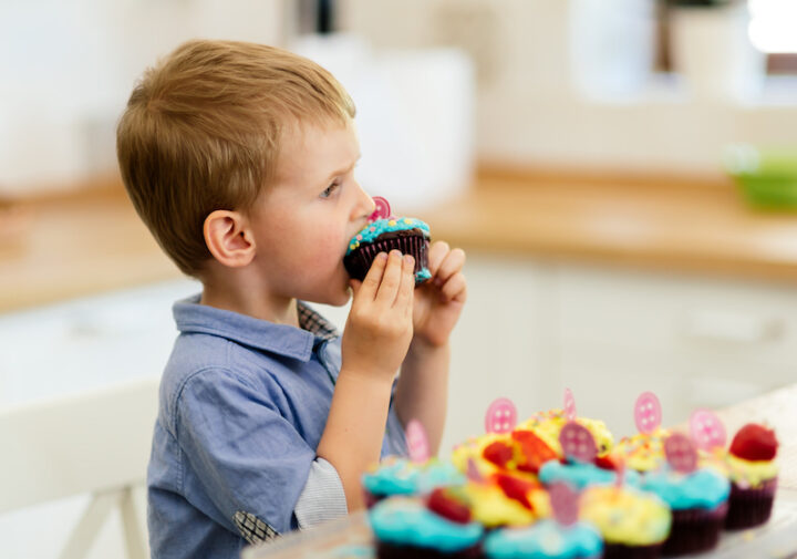 Child eating decorated beautiful muffins