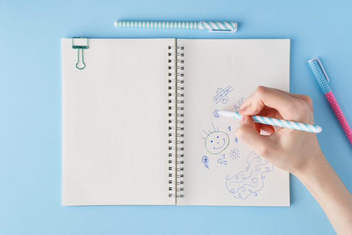 Hand draws scribble in a notebook. Blank notepad page in bullet journal on bright blue office desktop. Top view of modern table with notebook, stationery. Mock up, copy space