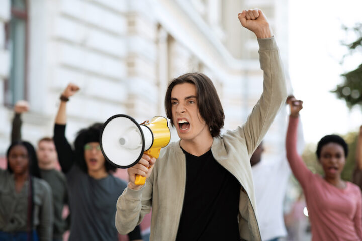 Leader of strikers young motivated man with loudspeaker yelling demands, raising fist up, leading international group of demonstrators fighting for human rights, against racism, for climate change