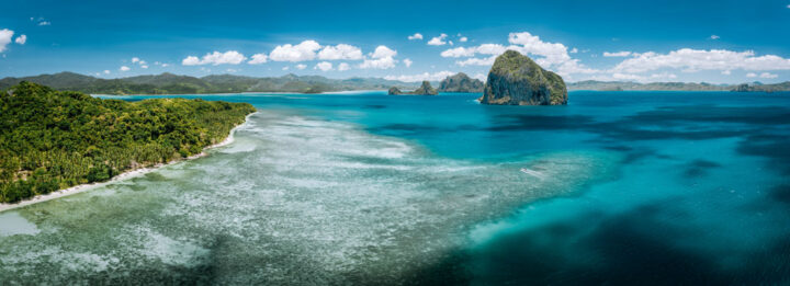 Aerial panorama of turquoise sea water, limestone cliffs and tropical sea shore