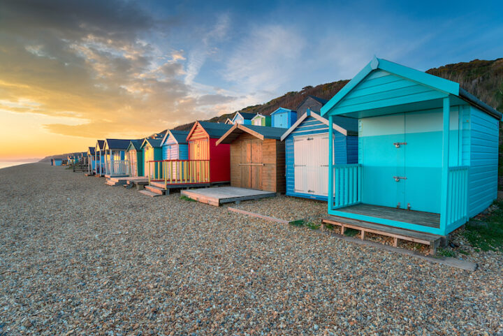 sunset over a row of brightly coloured beach huts at Milford on Sea on the Hampshire coast