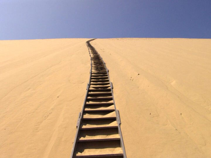 steps in sand dune going up towards a blue sky