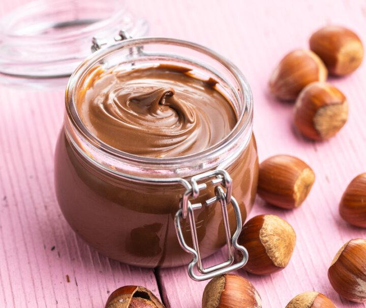 Sweet hazelnut spread. Chocolate cream in jar on pink table.