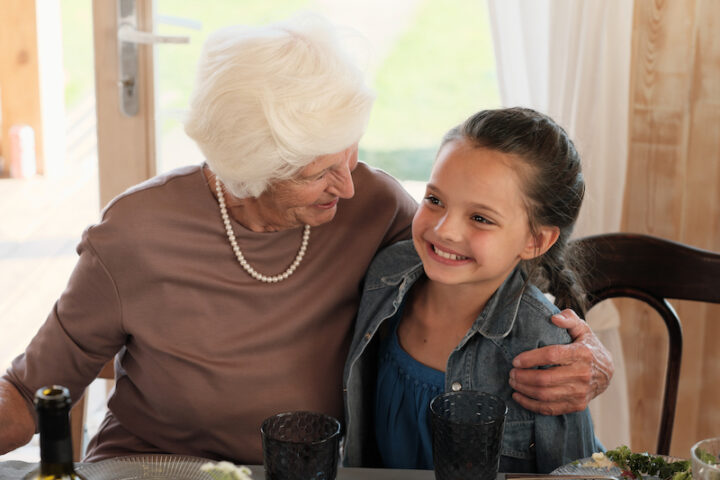 Happy grandmother embracing her smiling granddaughter while they sitting at the table and having dinner at home