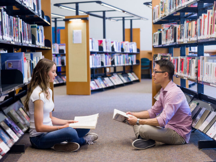 Two young students working together at the library