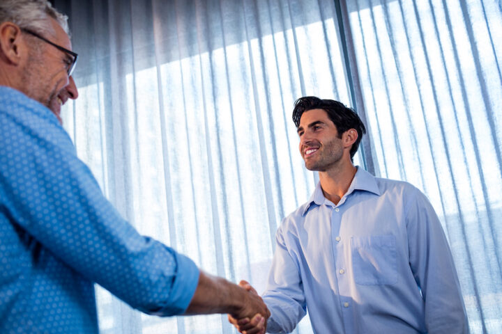 an old and young man giving a handshake in the office