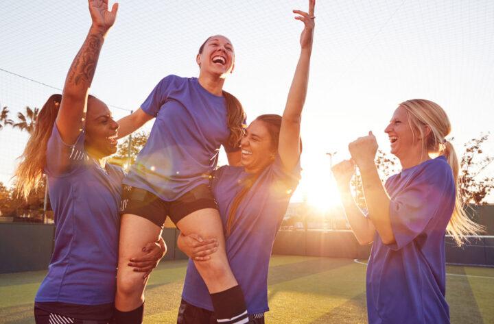 Womens Football Team Celebrating Winning Soccer Match Lifting Player Onto Shoulders