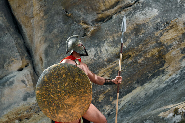 Portrait of a brave spartan warrior in a helmet and red cloak holding a shield and a spear resting outdoors on top of a rock