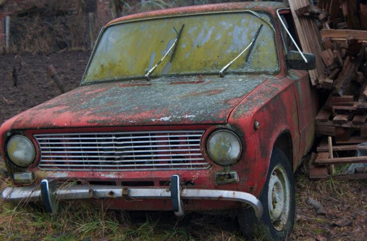 red old rusty car in scrapyard
