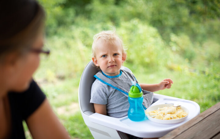 Offended and fussy little child boy during eating outdoor