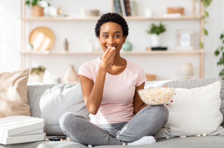 oung black woman munching popcorn in front of TV on comfy sofa at home