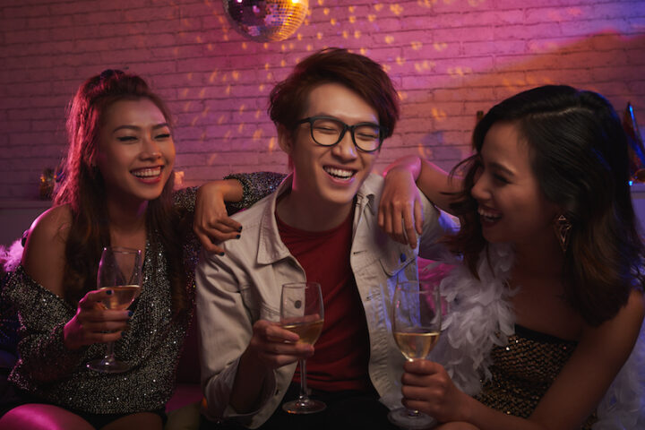 Vietnamese young people laughing and drinking champagne at party