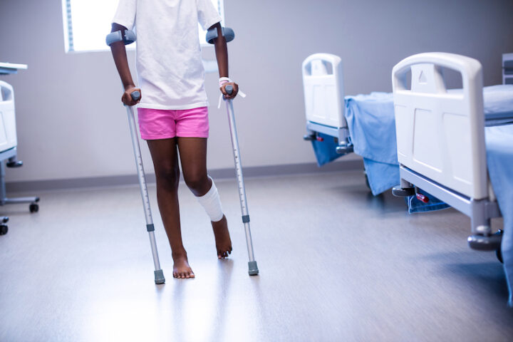 Girl walking with crutches in ward of hospital