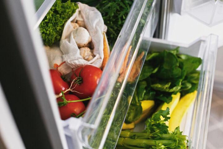Fresh vegetables in opened drawer in refrigerator. Plastic free carrots,tomatoes, mushrooms,radish,salad, arugula