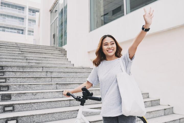 Happy young Asian woman with bicycle waving with her hands
