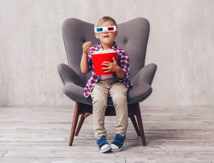 happy little kid with popcorn and 3d glasses sat on a grey chair in a empty room
