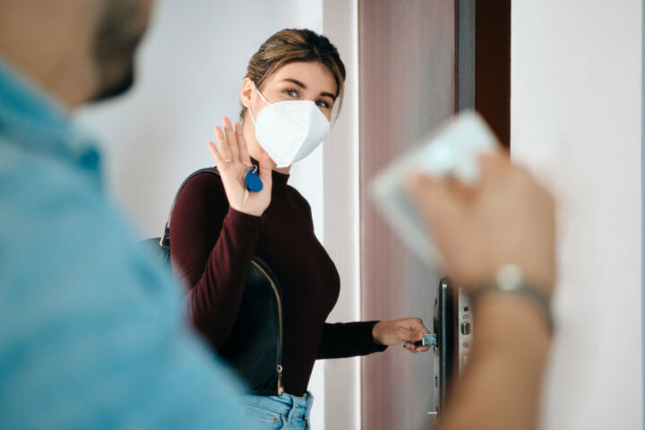 Woman going to work, wearing face mask and saying goodbye to partner
