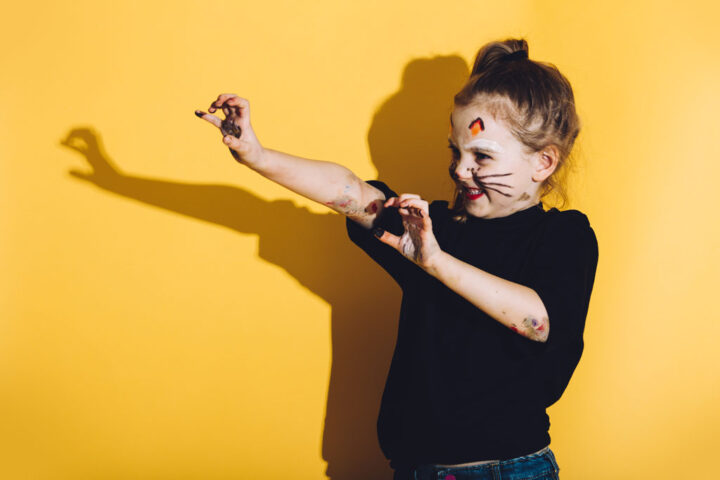 Young child with cat make up stretching her hands with yellow wall in the background