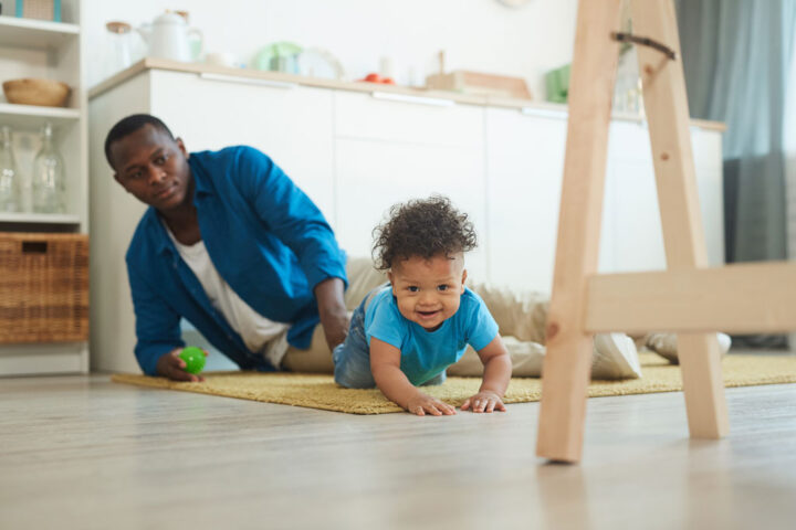 Portrait of cute African-American toddler crawling on carpet while playing with dad at home
