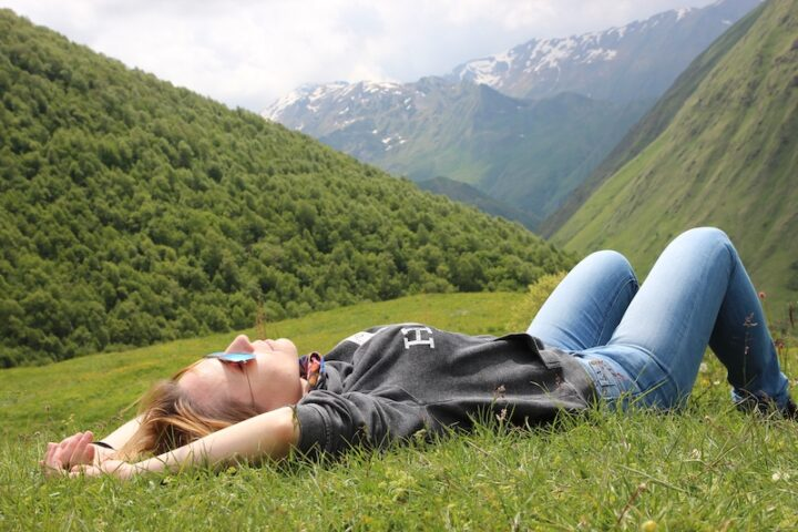 young woman with jeans and sunglasses lying down on the grass and enjoying the sunshine with mountains in the background