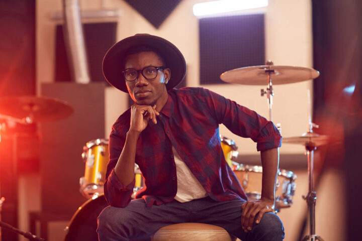 Portrait of contemporary African man looking at camera while posing in music recording studio