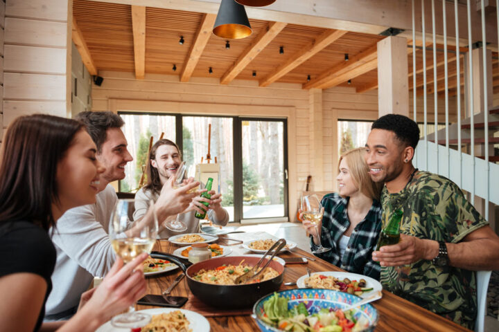 Group of cheerful young friends having dinner and laughing at the table at home