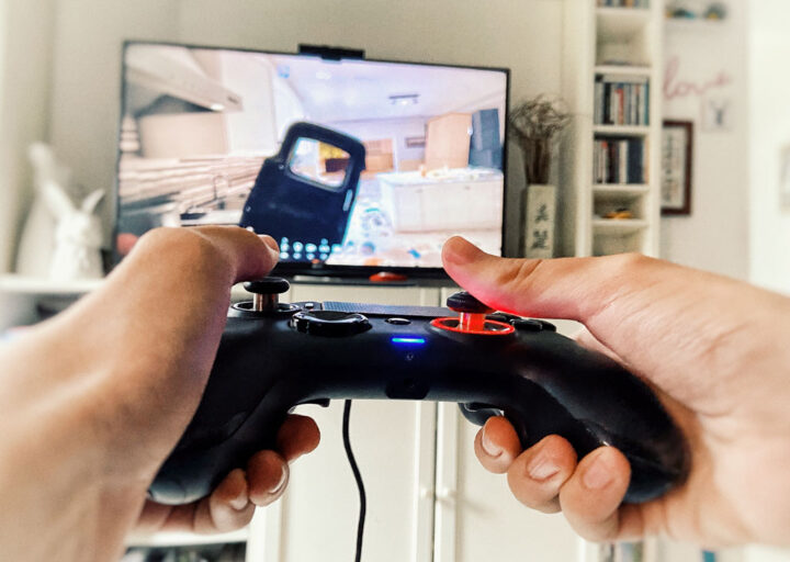point of view of a player with his hands holding PlayStation controller in front of a large TV screen