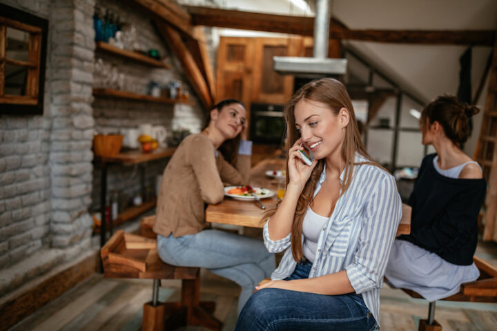 Cropped shot of an attractive young blonde having a phone call while having a breakfast with friends