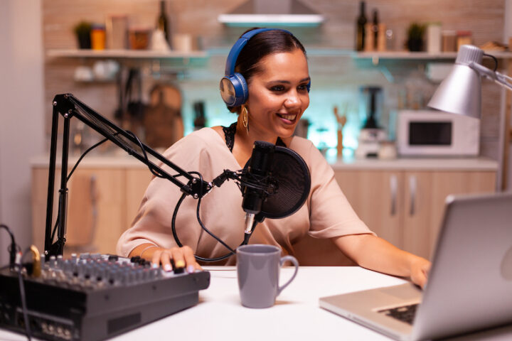 Speaking into professional microphone during podcast in home studio. Creative online show On-air production internet broadcast host streaming live content, recording digital social media communication