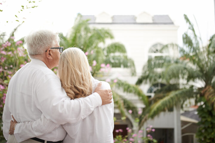 Rear view of hugging senior couple enjoying view from hotel balcony